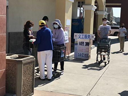 10月17日,聖荷西法輪功學員和退黨義工,在苗必達繁華交通路口展開真相橫幅,受到民眾支持。圖為民眾在打倒中共惡魔的徵簽表上簽名。 (大紀元)