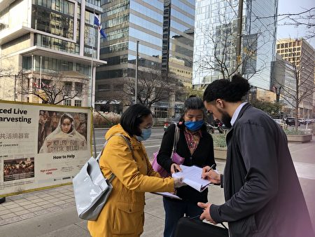 在市中心中領館簽證處,一位西人男士在《馬格尼茨基法案》制裁中共官員和「終止中共」兩份徵簽表上簽名時,用中文說:「中國政府不好,法輪功好。」(潘學峰提供)