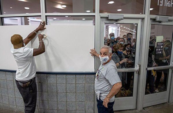 2020年11月4日,底特律市中心的TCF點票中心,投票站工作人員在窗戶上貼上了木板,阻止點票監視者監視點票區。(Seth Herald/AFP via Getty Images)