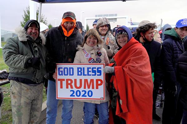 2020年11月2日,支持特朗普總統連任的民眾手舉「God Bless Trump 2020」看板,合照留念。(宋昇樺/大紀元)