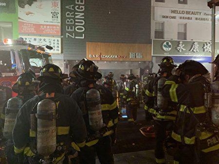 上百消防员到场救火,图为消防员在酒吧前。