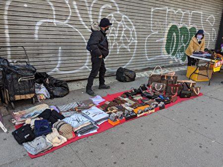 图为纽约法拉盛缅街上的摊商贩卖高端奢侈品皮包。