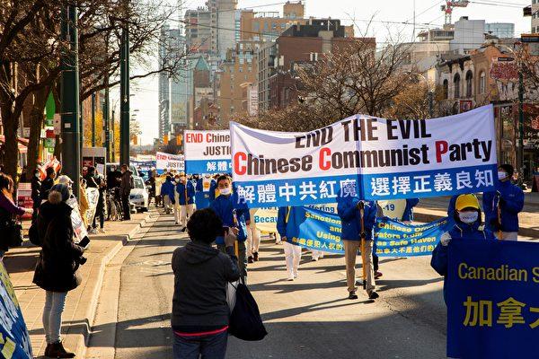 2020年11月14日下午,數百法輪功學員在多倫多市中心舉行「解體中共」盛大遊行,受到沿途市民關注。(艾文/大紀元)