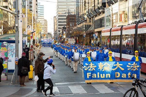 2020年11月14日下午,數百法輪功學員在多倫多市中心舉行「解體中共」盛大遊行,受到沿途市民歡迎。(艾文/大紀元)
