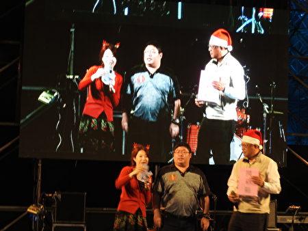 28日晚间,在布袋高跟鞋教堂圣诞音乐祭活动中,由立委蔡易余(中)当众抽出两个大奖,由两位幸运者各获得铝合金脚踏车乙辆。