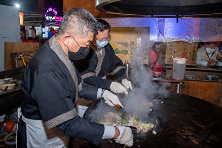 卫福部长陈时中与桃园市长郑文灿共同翻炒食物,与市民互动。