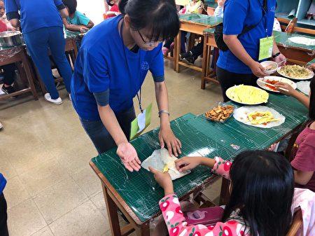 嘉大農藝志工指導學童包潤餅。