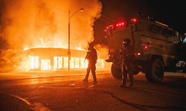 2020年8月24日,在威斯康辛州基諾沙市,一輛警察裝甲車在一個十字路口巡邏,遭暴亂者縱火的建築物正在燃燒。(Brandon Bell/Getty Images)