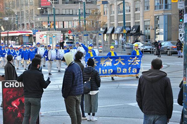 2020年11月14日下午,數百法輪功學員在多倫多市中心舉行「解體中共」盛大遊行,受到沿途市民關注。(周行/大紀元)
