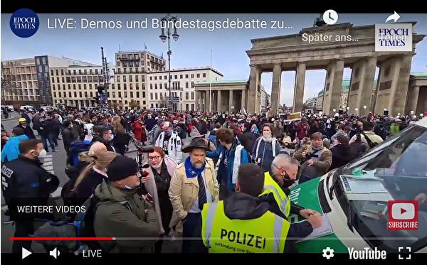 正跟警方交涉的艾里希先生(Alexander Ehrlich,中間穿米黃色風衣者),他來自奧地利維也納,是歐洲旅遊大巴協會「Honk for Hope」主席。(德文大紀元影片截圖)