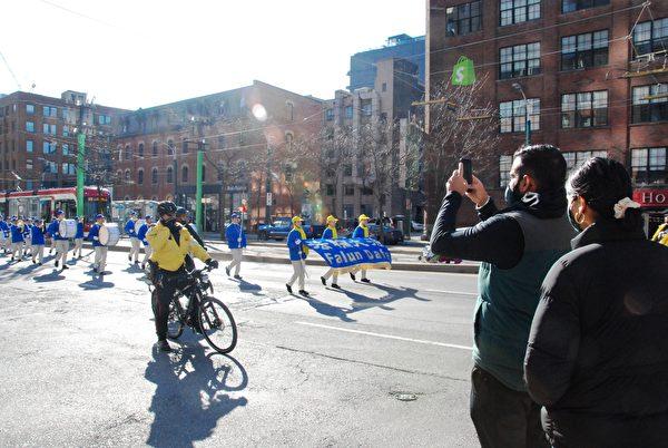 2020年11月14日下午,數百法輪功學員在多倫多市中心舉行「解體中共」盛大遊行,受到沿途市民關注。(伊鈴/大紀元)