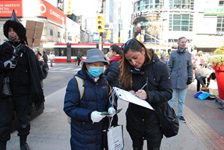 註冊按摩師蒂娜(Tina)簽名支持終止中共,她說:「瘟疫的源頭是中共,不是中國人。我支持中國人,但是反對中共,他們製造了病毒,造成世界大流行。必須終止中共。」 (伊鈴/大紀元)