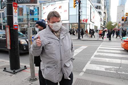 人文學教授布萊恩‧博克斯(Brian boks)路過丹達士廣場三退義工打的橫幅前,他給橫幅拍照,又對義工豎大拇指,並簽名支持終止中共。(伊鈴/大紀元)