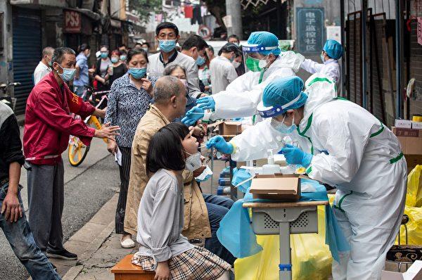 2020年5月15日,在中共病毒(俗稱武漢病毒、新冠病毒)疫情爆發最嚴重的中國湖北省武漢市,身穿防護服的醫務人員在小區內進行核酸檢測。(Photo by STR/AFP via Getty Images)