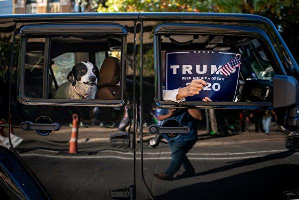 2020年11月7日,美國德州奧斯汀(Austin),總統特朗普的支持者開車經過拜登支持者的集會場所時,在車窗內舉著特朗普競選標語和國旗。(SERGIO FLORES/AFP via Getty Images)