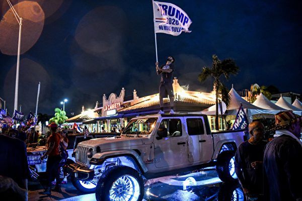 2020年11月7日,美國佛羅里達州邁阿密,在拜登被片面宣佈為總統選舉的獲勝者之後,一位特朗普的支持者在抗議活動中高舉旗幟。(CHANDAN KHANNA/AFP via Getty Images)