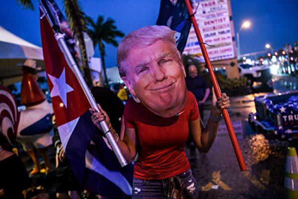 2020年11月7日,美國佛羅里達州邁阿密,在拜登被片面宣佈為總統選舉的獲勝者之後,一位戴著特朗普面具的支持者在抗議活動中舉著旗幟。(CHANDAN KHANNA/AFP via Getty Images)