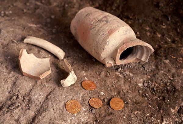 以色列古物局(IAA)11月9日表示,在耶路撒冷的考古挖掘中,意外挖到一個小陶罐,裏面裝了4枚保存完好的純金金幣。(MENAHEM KAHANA/AFP via Getty Images)