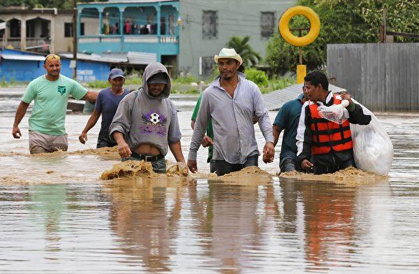 2020年11月18日,洪都拉斯聖佩德囉囌拉(San Pedro Sula),颶風艾奧塔(Iota)侵襲過後引發洪災,民眾在街上涉水通行。(WENDELL ESCOTO/AFP via Getty Images)