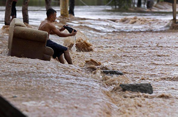 2020年11月18日,洪都拉斯埃爾普羅格雷索(El Progreso),颶風艾奧塔(Iota)侵襲過後引發洪災,街上一位居民將他鞋子裏面的水傾倒出來。(STR/AFP via Getty Images)