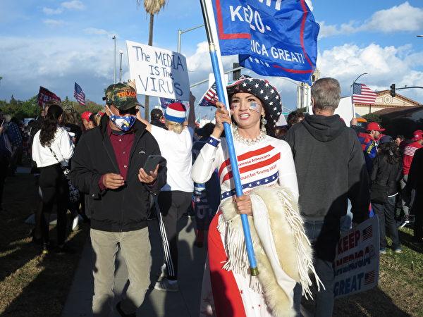 身穿傳統服裝的越南裔女子舉著特朗普2020的大旗,表達「越南裔支持特朗普!」(李梅/大紀元)