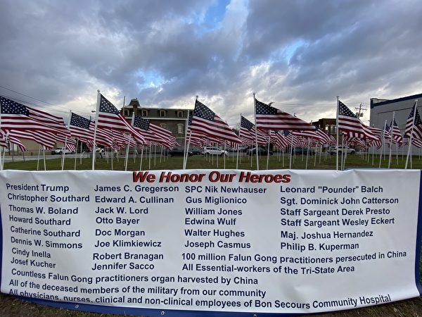 在「我們向英雄致敬」的活動banner上,上面標註有「授予在中國遭受迫害的一億法輪功學員」和「授予被中國(中共)強摘器官的成千上萬的法輪功學員」的內容。(李桂秀/大紀元)