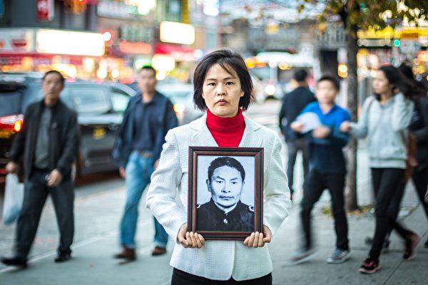 2015年11月1日,李江(音譯)女士在紐約皇后區的法拉盛拿著父親的照片,李父因修煉法輪功被中共迫害致死。(Benjamin Chasteen/Epoch Times)