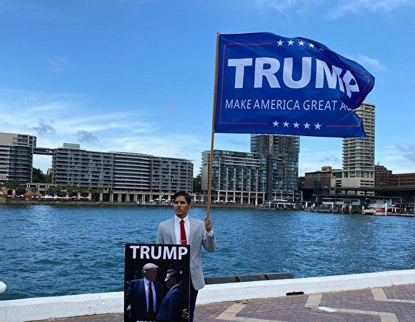 參加當天集會的保守主義活動人士格魯瓦爾(Samraat Joshua Grewal)表示特朗普連任有利澳洲。圖為格魯瓦爾在環形碼頭手舉支持特朗普—讓美國再次偉大的旗幟。(李睿/大紀元)