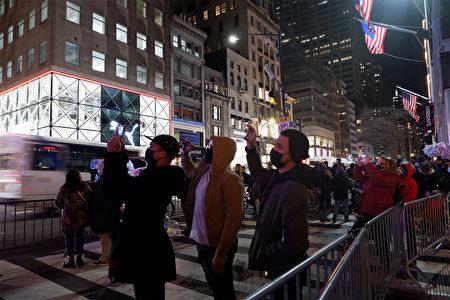 """2020年12月5日,纽约市曼哈顿""""第五大道百货公司""""的声光秀吸引路人拍照留念。"""