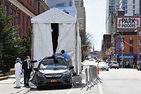 一輛靈柩車從紐約市布碌崙醫院外的冷藏卡車中運走屍體。