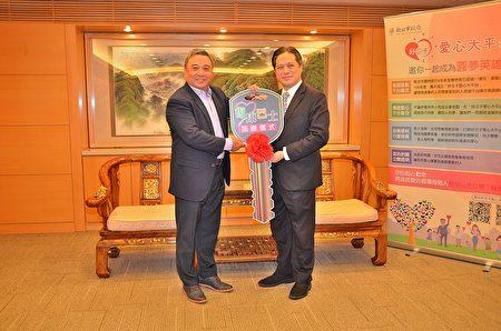 日電貿集團副董事長李坤蒼〈左〉代表捐贈2輛復康巴士給新北市政府,由副市長吳明機〈右〉受贈