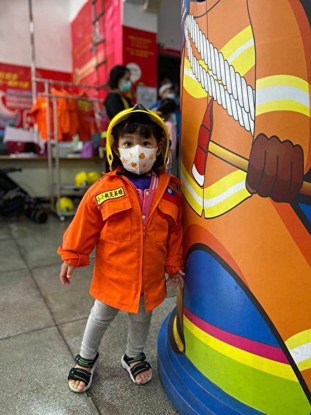 """新竹市消防博物馆备有消防衣,让孩子穿上变身小小消防员,跟古董消防车""""金德号""""合影留念。"""