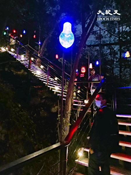 《回歸》是將與當地居民共同彩繪的燈泡懸掛展區長梯上,黑暗中點點黃光向上延伸匯聚於長梯盡頭。