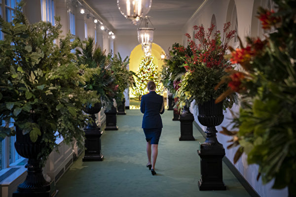 2020年11月30日,一名軍事助手在穿過位於華盛頓特區的白宮東柱廊。今年白宮聖誕節裝飾的主題是「美麗的美國(America the Beautiful)」。(Drew Angerer/Getty Images)