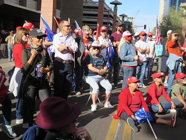 11月30日,現場聲援的民眾在亞利桑那州鳳凰城凱悅酒店外觀看新唐人電視台現場直播關於選舉舞弊聽證會的實況。(李梅/大紀元)