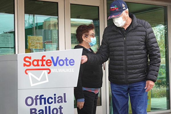圖為2020年10月20日,威斯康辛州密爾沃基(Milwaukee, Wisconsin),選民向投票箱中投遞選票。(Scott Olson/Getty Images)