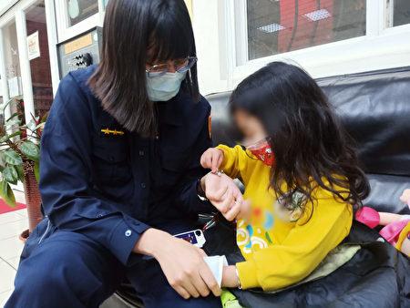 警员刘心妤扮起大姊姊递给女童暖暖包、热水及儿童用口罩,安抚孩童。