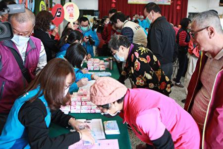 吴沙社区民众到社区活动中心办理兑换存折。