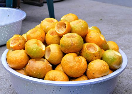 先用特製的金屬圓筒在虎頭柑頂部切割出一個圓缺口,再用湯匙細心地挖去果肉,再把空心的虎頭柑堆疊在塑膠圓盆裡。