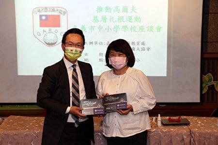 """中华民国高尔夫球协会理事长王政松(左)致赠市长黄敏惠""""国家培训队专属用球"""",期盼未来几年能有来自嘉义市从小培训的学童,成为高尔夫台湾之光选手。"""