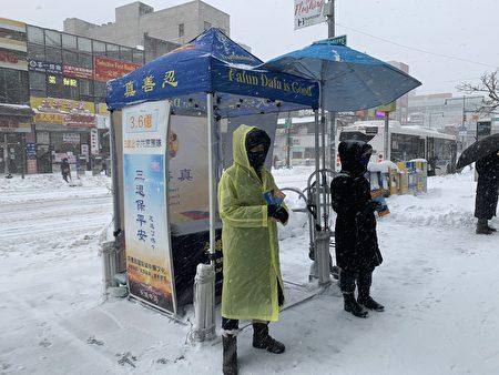 法轮功学员顶风冒雪,坚持每天向过往的民众传递法轮大法好的福音。