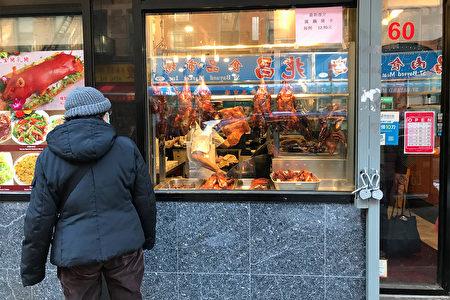 图为2021年2月8日,纽约华埠一位妇人驻足观看橱窗内的烧腊。