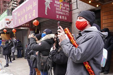 2021年2月12日,游客拍摄纽约华埠中华公所与属下60侨团邀请的舞狮表演。