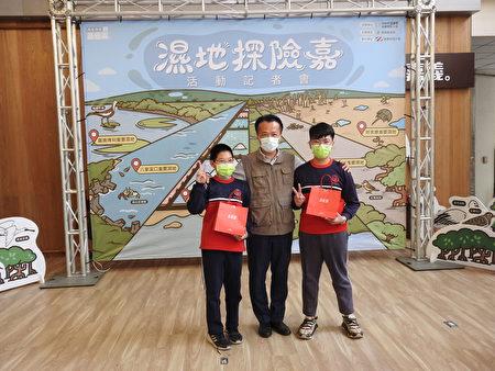 """在""""嘉义县湿地生态环境教育系列活动""""行前记者会中,县长翁章梁(中)进行有奖征答,并颁奖给两位得奖的小朋友。"""