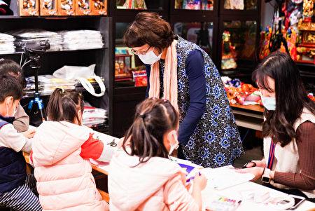 全联善美的文化艺术基金会罗欣怡执行长与台湾学童一起制作龙面具。