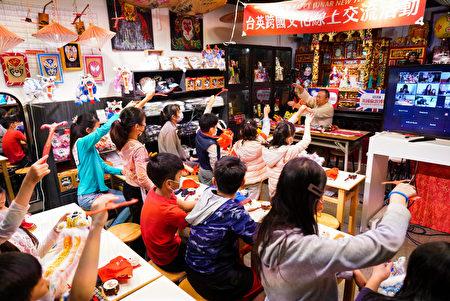 河洛坊布袋戏林铭文老师教导两国孩童学习布袋戏操偶。