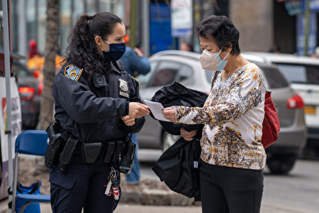 警官在曼哈顿唐人街街上向华人妇女派发传单。图片摄于2021年3月17日。