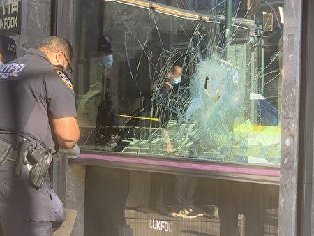 「六福珠寶」的櫥窗被砸爛,歹徒從洞口伸手進去偷走珠寶,警方在現場調查。