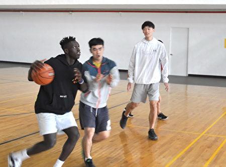 阿比伯與醒吾籃球隊隊員練習帶球過人,神情專注。