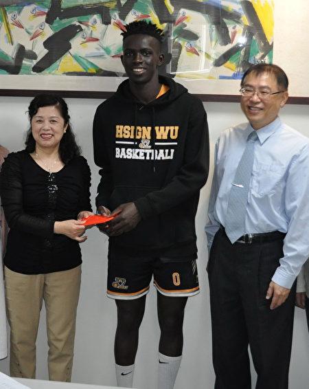 前林口高中家長會長林巧菁(左)捐贈獎助金給阿比伯,醒吾科大校長陳義文(右)鼓勵。